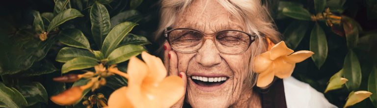Elderly woman smiling brightly with a full set of beautiful teeth among summer flowers. Banner for Skip Buyer's Remorse blog post.